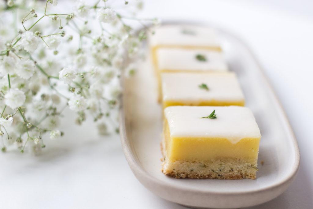 Habt ihr schon mal Thymian mit Zitrone zusammengebracht? Für mich funktioniert es perfekt. Der süß-salzige Mürbeteig mit Thymian-Aroma, die leicht saure, fruchtige Zitronen-Creme und der süße Guss harmonieren so gut. #backen #backrezepte #zitronenschnitten #thymian #baking #thyme #lemonbars #lemonthymebars